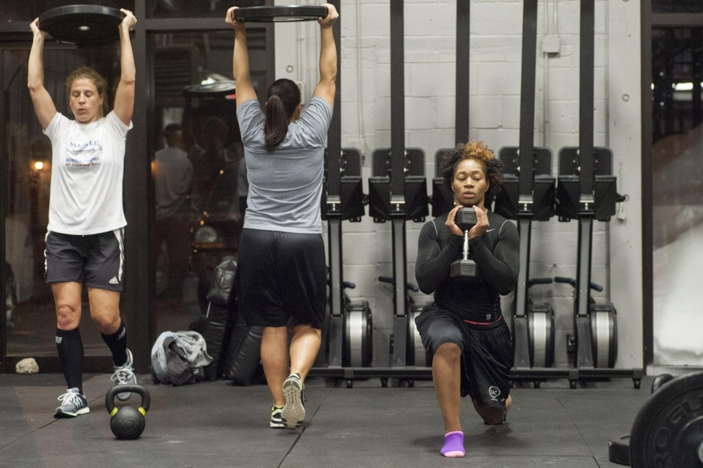From left: Renegades Sue Quimby, Kimberly Boroyan, and Asia Asanté do conditioning exercises at Crossfit 128 in Wakefield, February 26, 2015. Quarterback Allison Cahill (not pictured) who works as a personal trainer, led the team through conditioning workouts at their first practices(Wicked Local Staff Photo/ Sam Goresh)