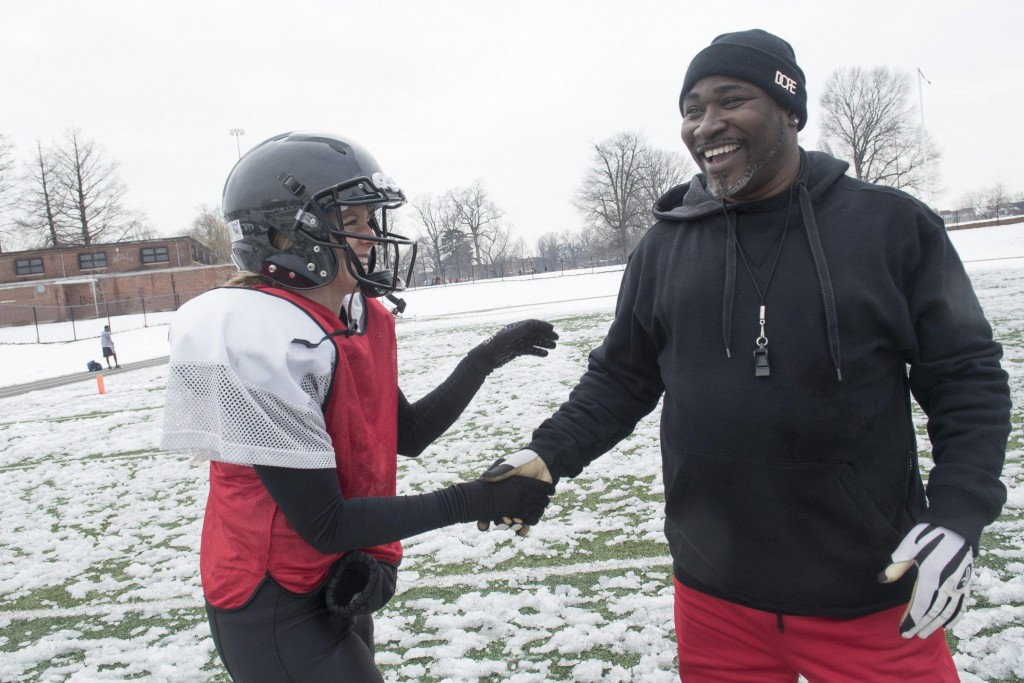 Renegades quarterback Allison Cahill laughs with head coach Donnie Williams after their scrimmage against the Independent Women's Football League's Washington Prodigy in Philadelphia, March 21, 2015. (Wicked Local Staff Photo/ Sam Goresh)