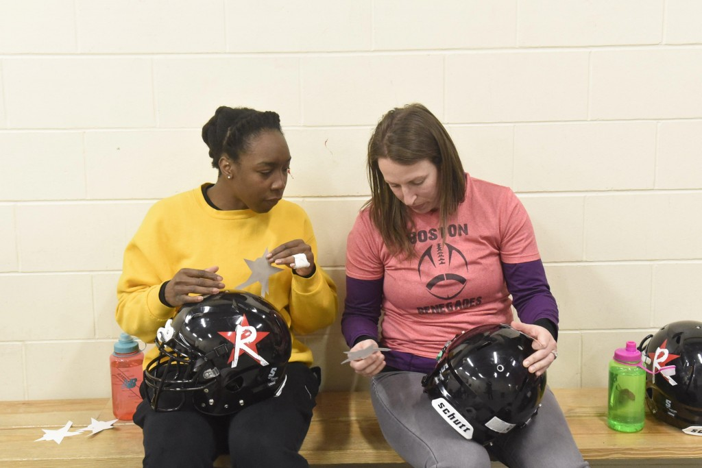 Renegades running back Whitney Zelee (left) and tight end Emily Weinberg (right) work to apply their Renegades logo stickers onto their helmets at their last practice before their home opener, April 16, 2015.(Wicked Local Staff Photo/ Sam Goresh)