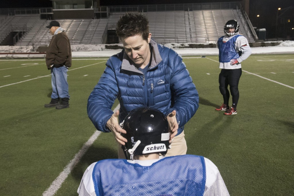 Renegades trainer Michelle Kelley helps a player adjust her helmet so that it fits properly at their practice at Dilboy Stadium, March 23, 2015. (Wicked Local Staff Photo/ Sam Goresh)