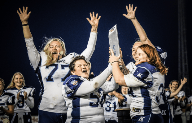 Kuusinen #34 (right) hoists the 2019 IFAF Women's European Championship trophy with teammates on the Finnish national team. <nobr>Photo: Linda Mustakari</nobr>
